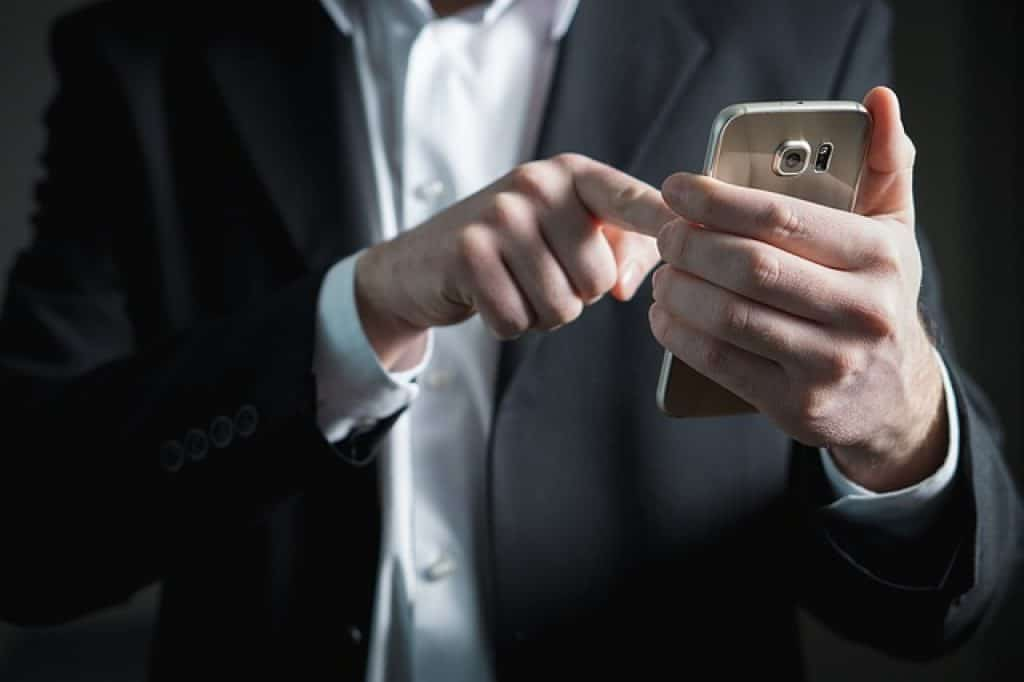 homme qui manipule son smartphone
